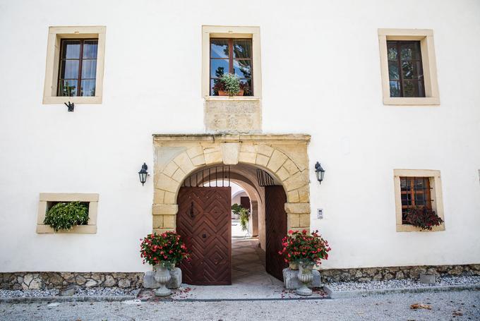 Vhod v grad Tuštanj, pred katerim stoji tudi 350-letna platana. Objekt so zgradili leta 1490, o čemer pričajo grbi nad vhodnim portalom gradu.