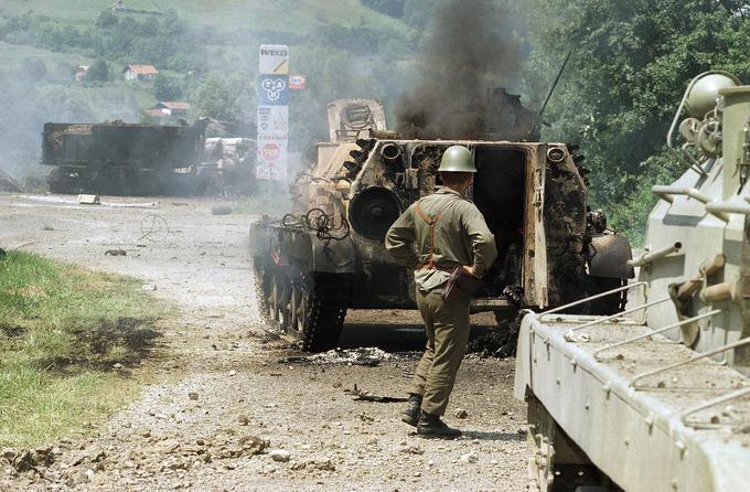 Vojak JLA stoji ob uničenem oklepniku.