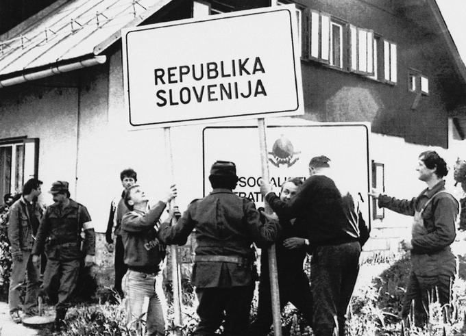 Slovenski teritorialci in civilisti odstranjujejo tablo z napisom Socialistična federativna republika Jugoslavija in postavljajo tablo z napisom Republika Slovenija. Fotografija je bila posneta po slovenskem zavzetju mejnega prehoda Jezersko 29. junija 1991.