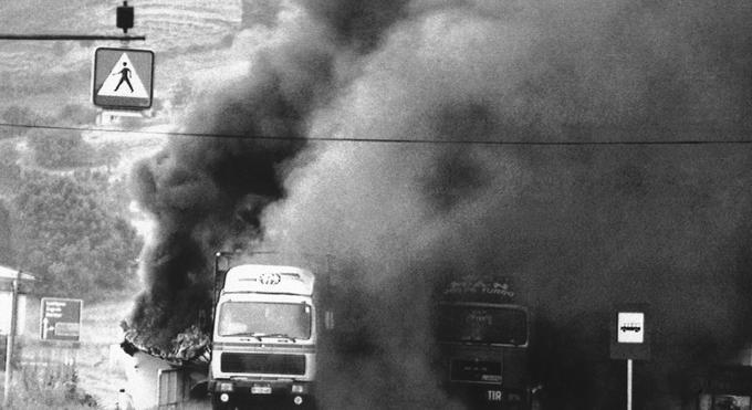 Goreča tovornjaka pri Pesnici, ki so ju zadeli tankovski izstrelki. Fotografija je bila posneta 27. junija 1991.